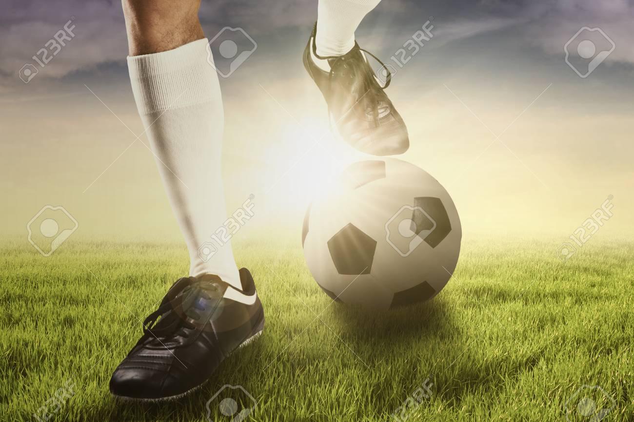 Foto de archivo - Pie del jugador de fútbol con una pelota para el  entrenamiento patear una pelota 87fdd1ddea706