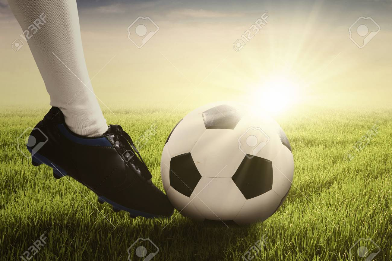 f544244a4e9 Close up of foot of soccer player wearing football shoe and and kicking a soccer  ball