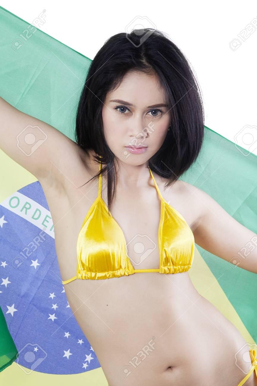 ab178107236 Beautiful young woman wearing yellow bikini while holding Brazilian flag in  the studio, isolated on