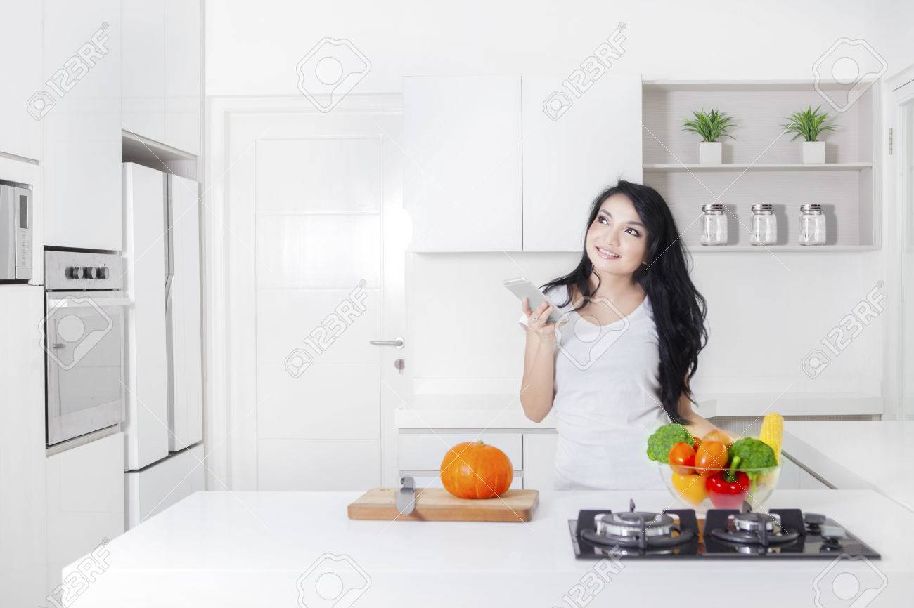 young woman cooking in the kitchen while holding a mobile phone