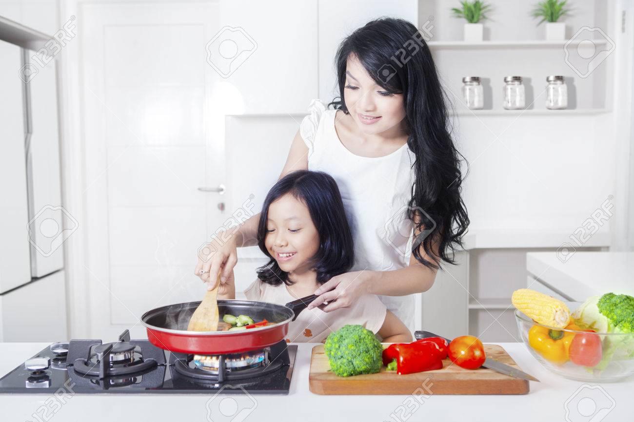 Portrait d'une belle femme et sa fille cuisinant un légume avec une friture dans la cuisine Banque d'images - 63532412