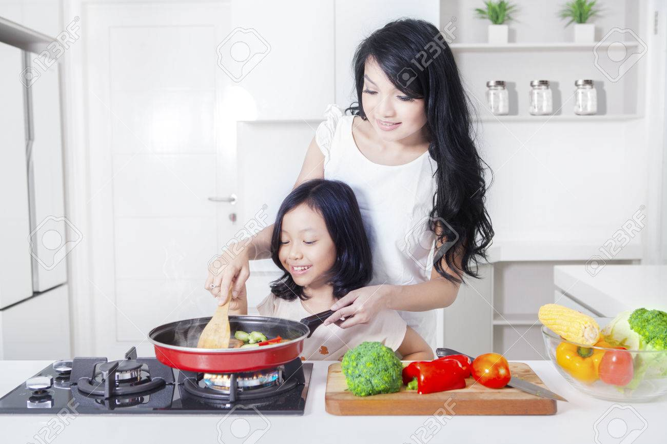 Portrait of a pretty woman and her daughter cooking vegetable with a frying in the kitchen Banque d'images - 63532412