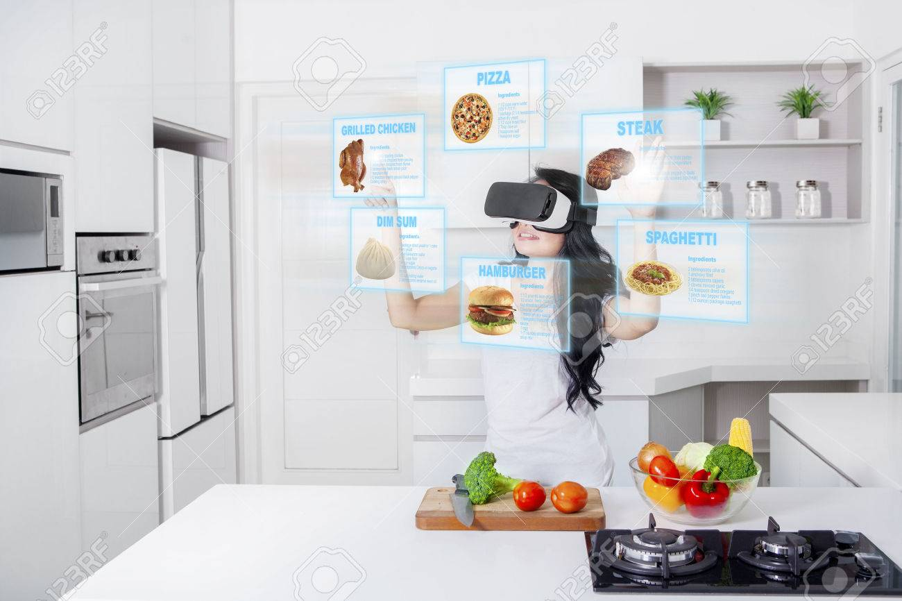 Virtual Reality Keuken : Young woman cooking in the kitchen while wearing virtual reality