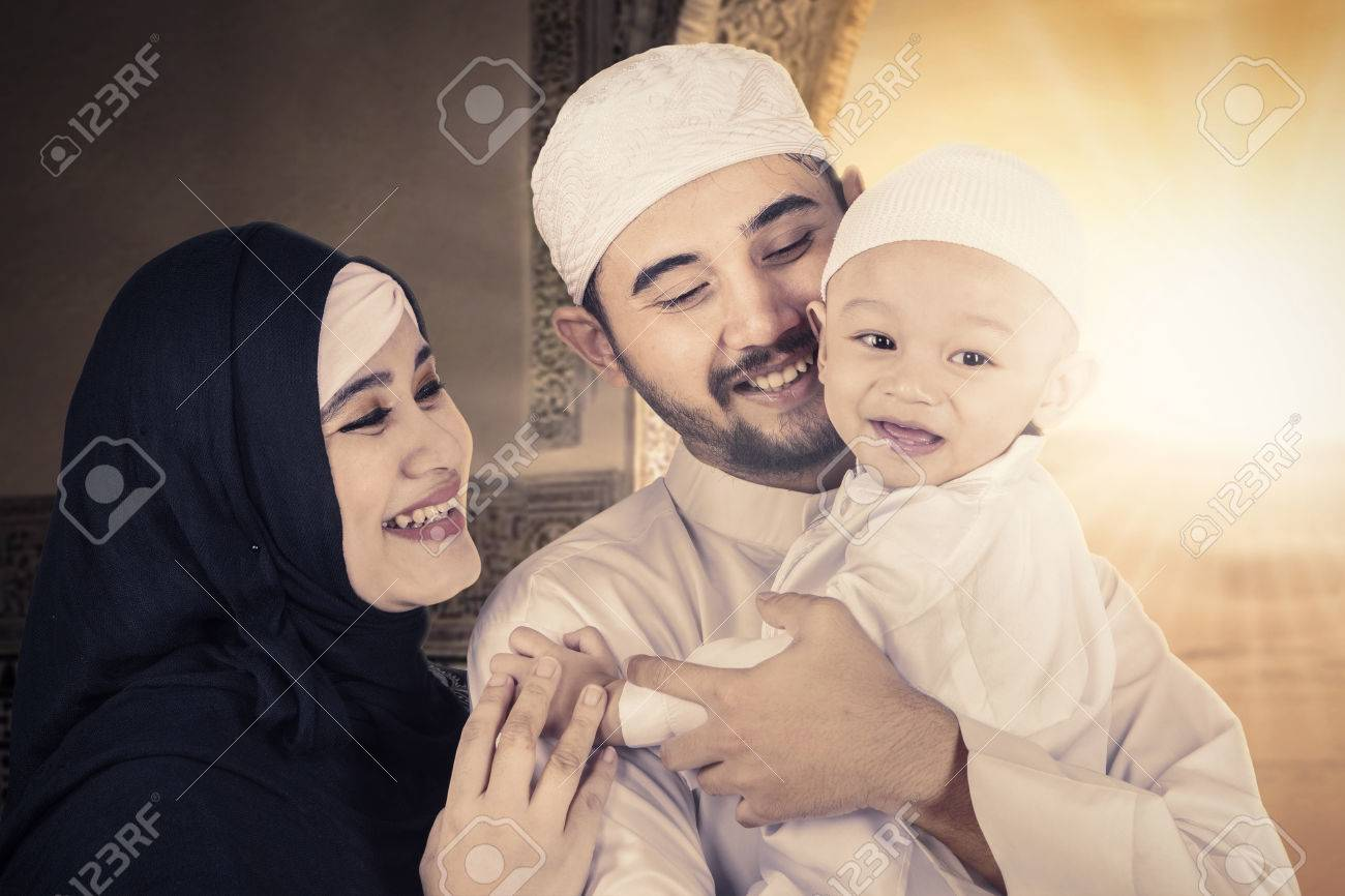 Muslim happy family hugging their cute baby while smiling and standing at home stock photo