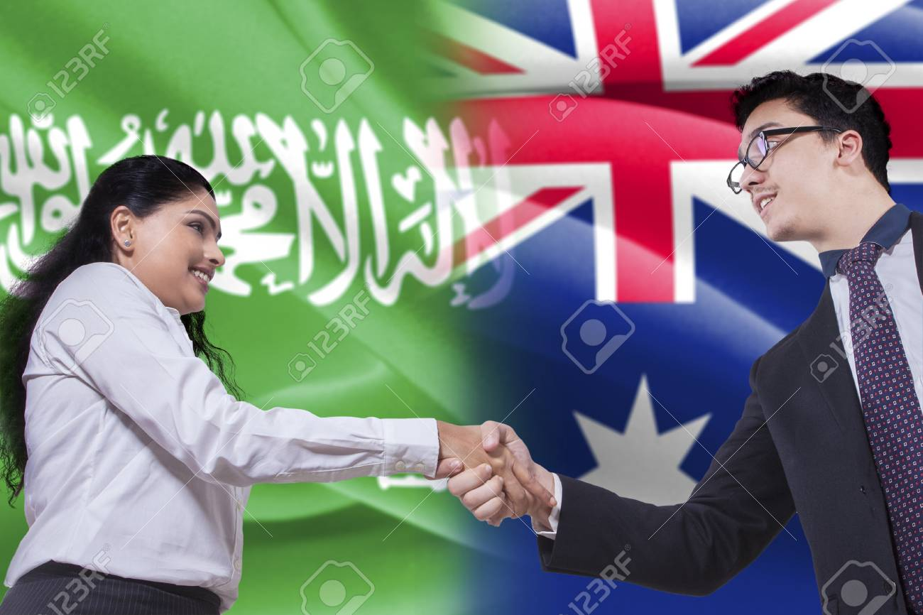 Photo of a young Australian businessman shaking hands with Arabian businesswoman in front of Australian and Arabian flags Stock Photo - 66321871