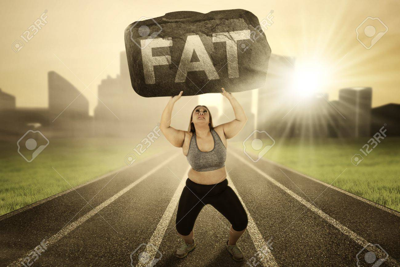 Picture Of Overweight Woman Lifting A Boulder With Fat Word While Stock Photo Picture And Royalty Free Image Image 67352543