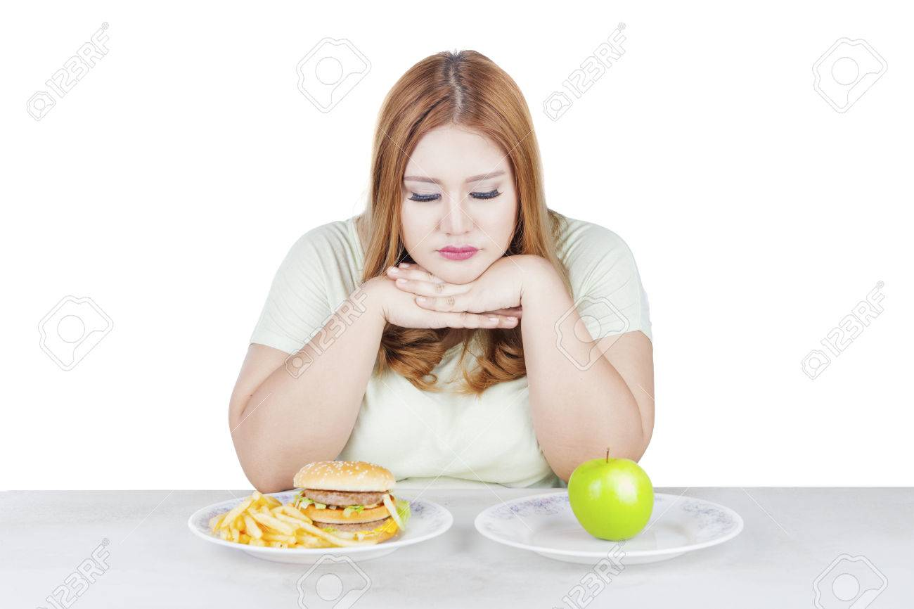 Portrait of overweight woman looks doubtful to choose a fresh apple fruit or hamburger, isolated on white background Banque d'images - 67352794