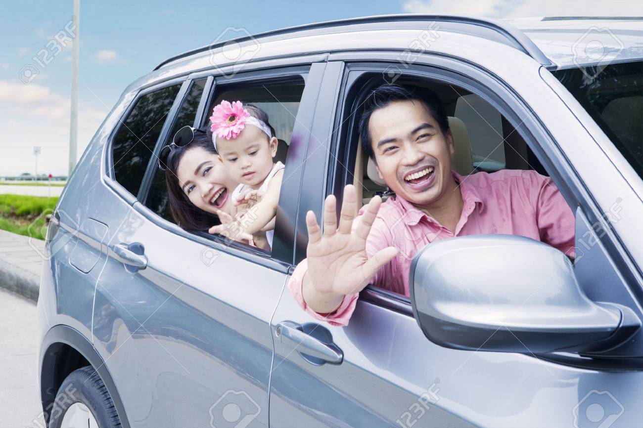 Portrait of happy family looking out car window while smiling at the camera in the highway - 70646389