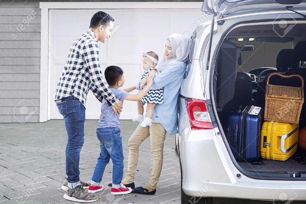 Picture of Muslim parents with their children ready to trip while standing near a car in the house garage Banque d'images - 77317744