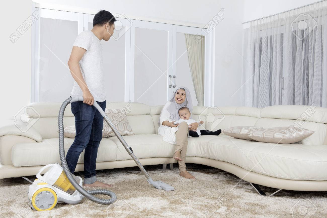 Young Man Cleaning Carpet With Vacuum Cleaner While His Wife Stock