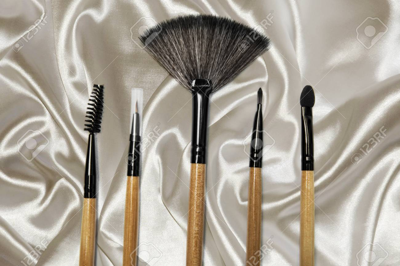 Top View Of Various Cosmetic Brushes For Makeup Above Fabric Stock