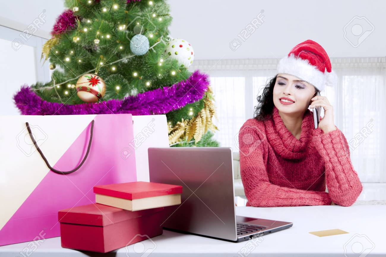 Young Indian Woman Buying Christmas Gifts Online By Using A ...