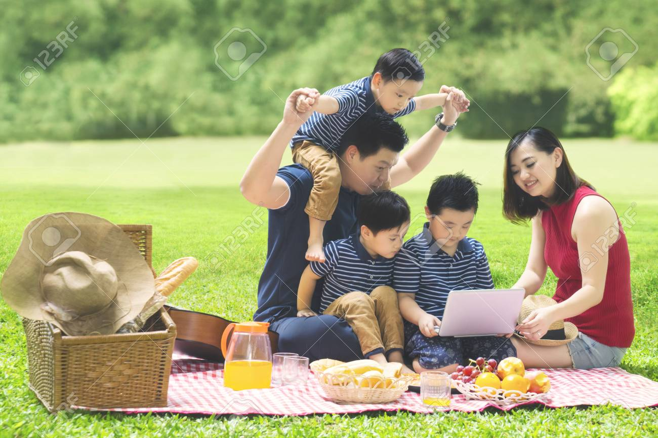Image of Asian family using a laptop while enjoying holiday and picnicking in the park - 93130677