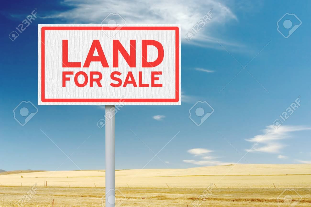 Land for sale sign against empty field and blue sky stock photo 96442384