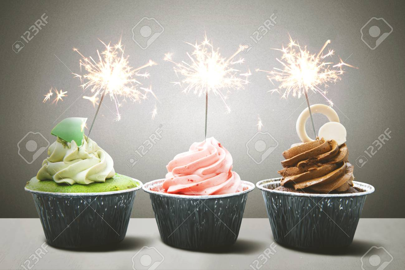 Row Of Colorful Birthday Cupcakes With Sparklers Above Table Stock Photo