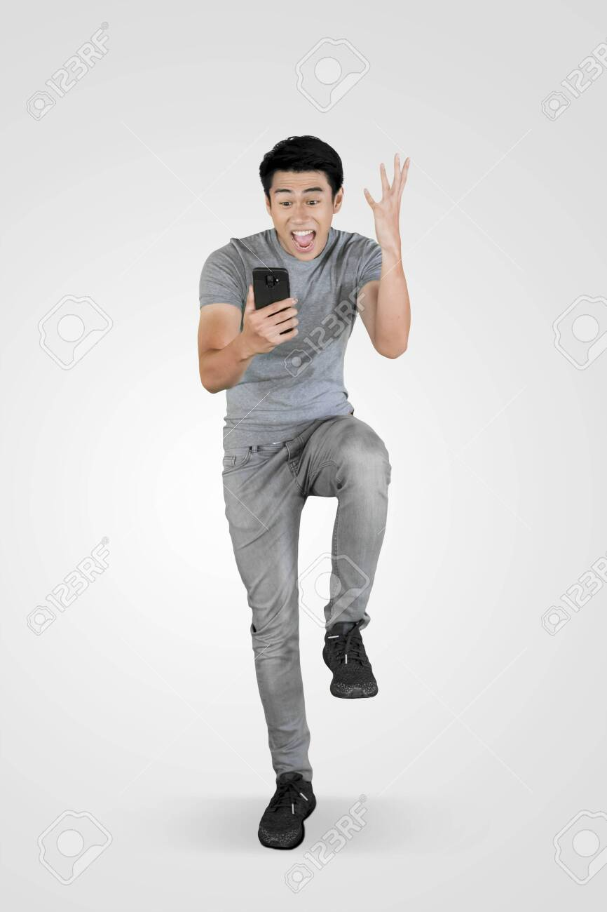 Full length of young Asian man looks shocked while using a mobile phone in the studio - 127327885