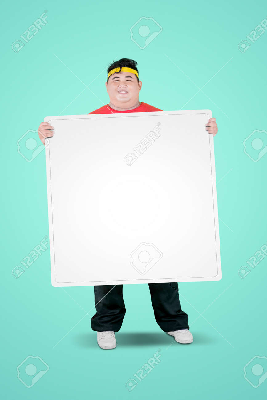 Portrait of an obese man wearing sportswear while holding a blank whiteboard in the studio - 157694129