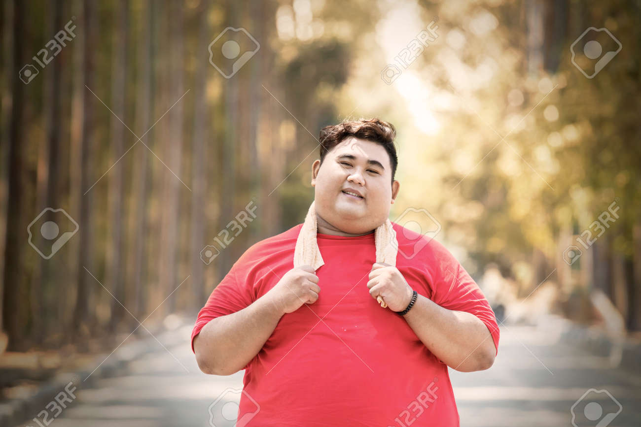 Portrait of Asian fat man wearing sportswear while standing on the road at autumn time - 157694114