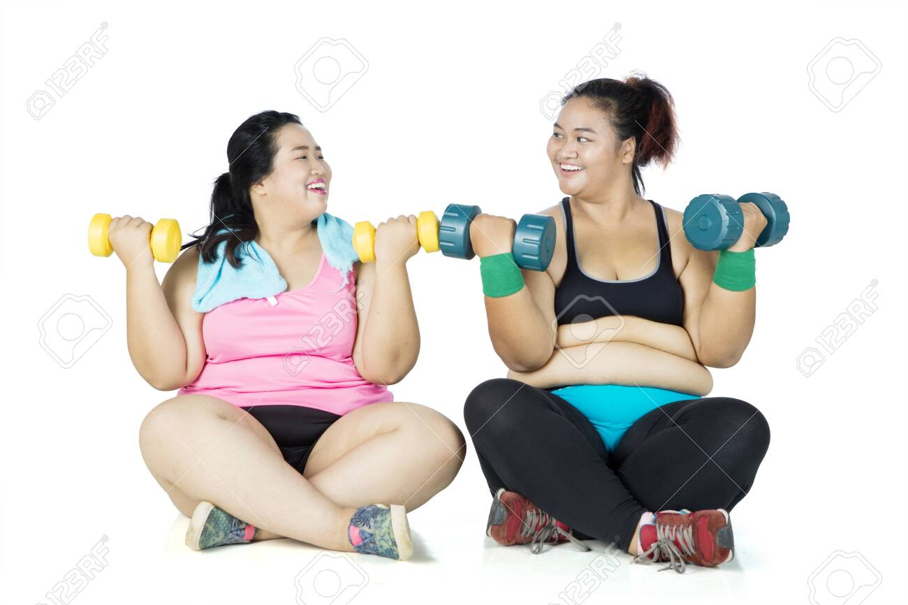 Two overweight women exercising with dumbbells while sitting in the studio, isolated on white background - 141344804