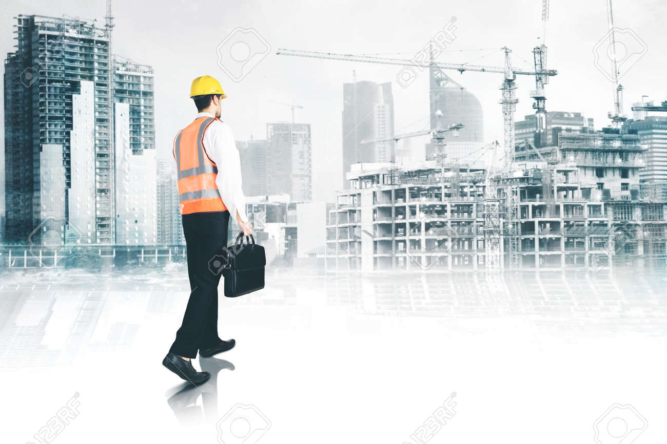 Rear view of male engineer carrying a suitcase while walking toward construction site project - 169346583