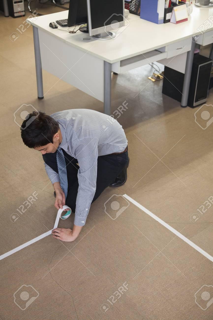 junger geschäftsmann das abkleben der boden im büro lizenzfreie