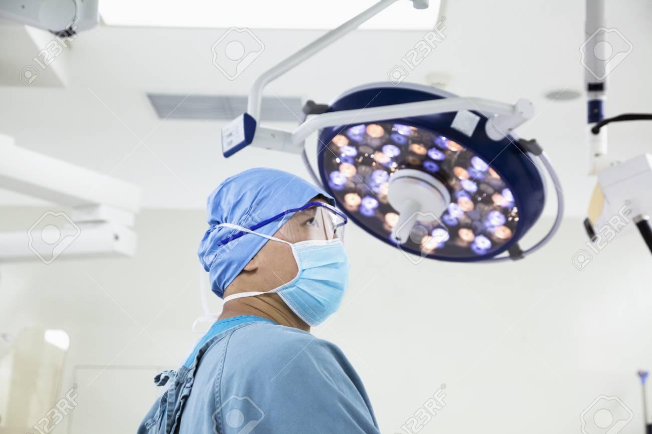 外科医が手術室で手術用マスクとメガネを着用の側面図 の写真素材画像
