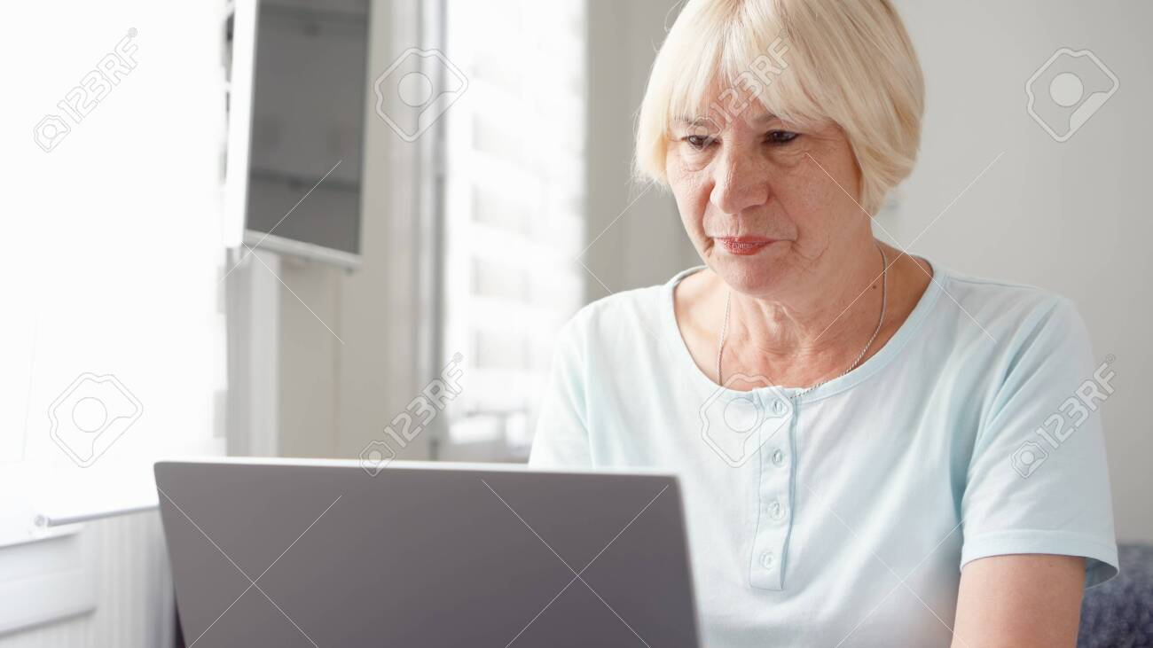 Elderly senior blond woman working on laptop computer at home. Remote freelance work on retirement, active modern lifestyle of older people. - 123737481