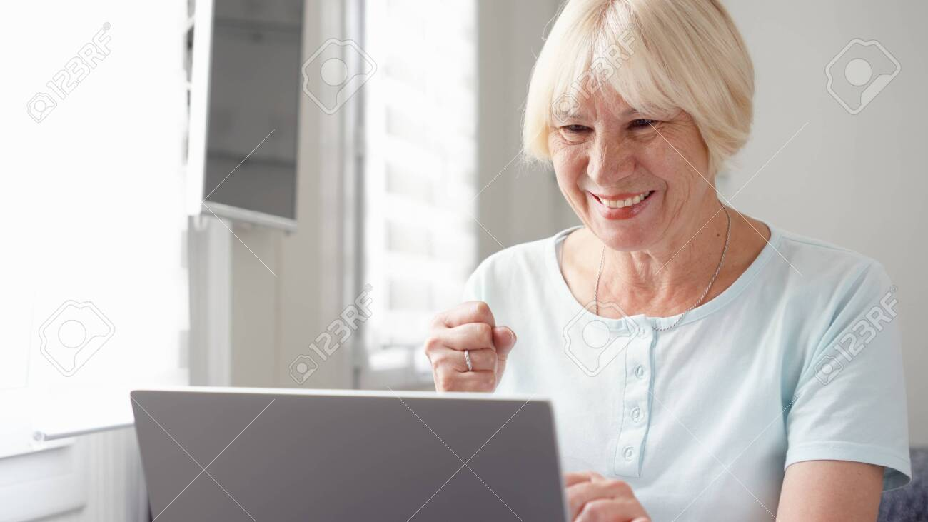 Elderly senior blond woman working on laptop computer at home. Received good news excited and happy. Remote freelance work on retirement, active modern lifestyle of older people. Success concept - 123737483