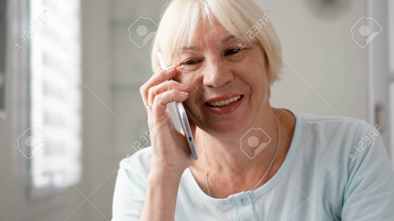 Good-looking blond senior woman sitting at home using smartphone. Retired woman talking on cellphone. Active modern elderly people concept - 123737486
