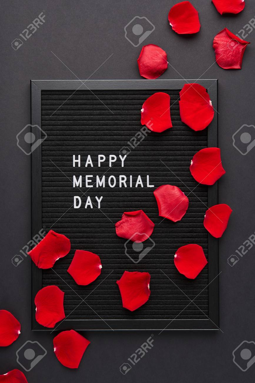 black letterboard with white plastic letters with quote happy memorial day and rose petals on