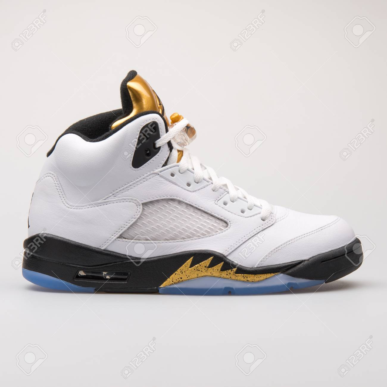 9306455b Stock Photo - VIENNA, AUSTRIA - JUNE 14, 2017: Nike Air Jordan 5 Retro  white, black and gold sneaker isolated on grey background