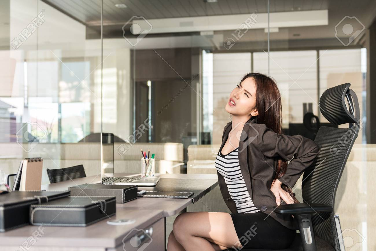 Young businesswoman having back pain while sitting at office desk Stock  Photo