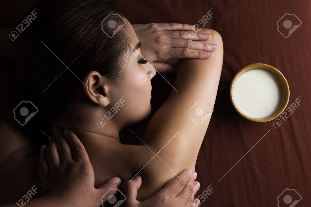 Asian woman having massage and bowl of milk , spa salon Beauty treatment  Stock Photo -