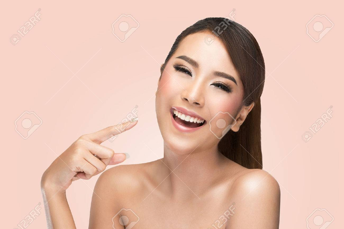 skin care beauty woman pointing her face and laughing smiling happy and cheerful. Asian female beauty model on pink background. Stock Photo - 47651191
