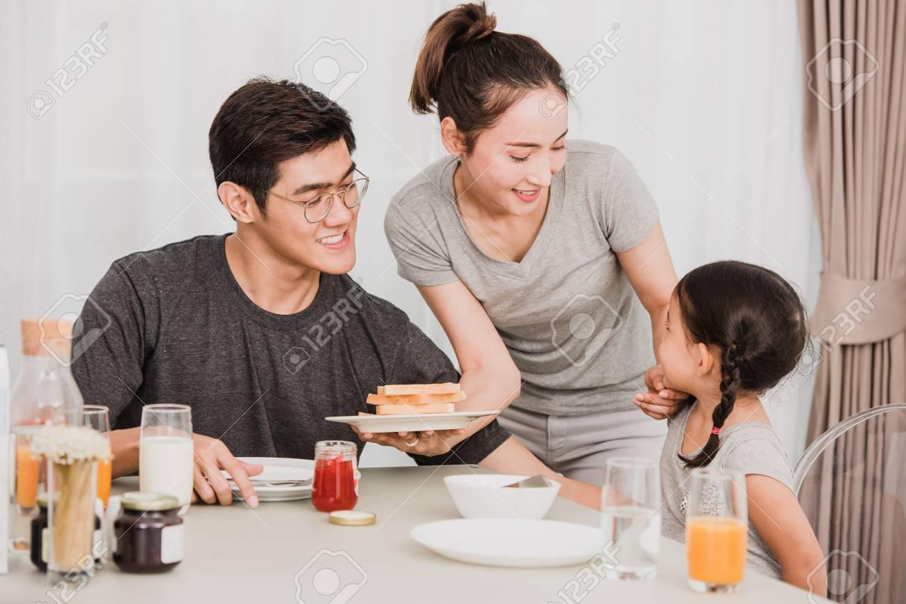 Happy family having breakfast at home - 94858915