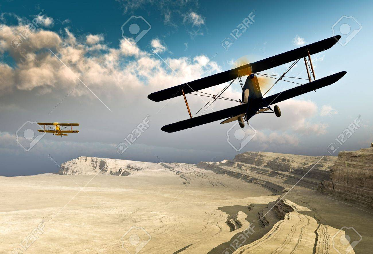 Two Vintage WWI Double Wing Planes Flying Over A Canyon Stock Photo