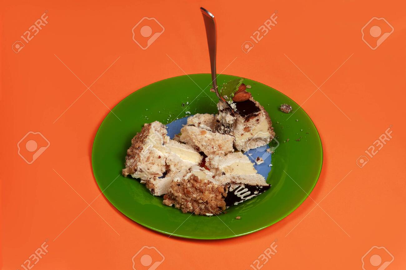 Green Dirty Plate With Many Broken Pieces Of Cream Cake And Fork Sticking Out Anti Diet Concept Unhealthy Dessert Passion For Sweets Bad Calories Coral Background Copy Space Lizenzfreie Fotos Bilder Und