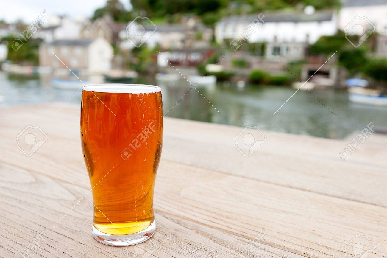 A Full Pint Of English Real Ale On A Wooden Table Outside A Riverside Pub  Differential