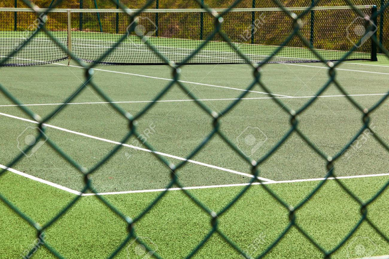 A view of an empty tennis court through the course fence. Stock Photo - 16541602