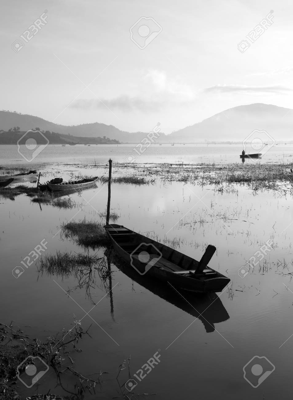 The quiet lake in early morning with black   white tone, fishermen make living on there, boat reflect on surface water Stock Photo - 23117012
