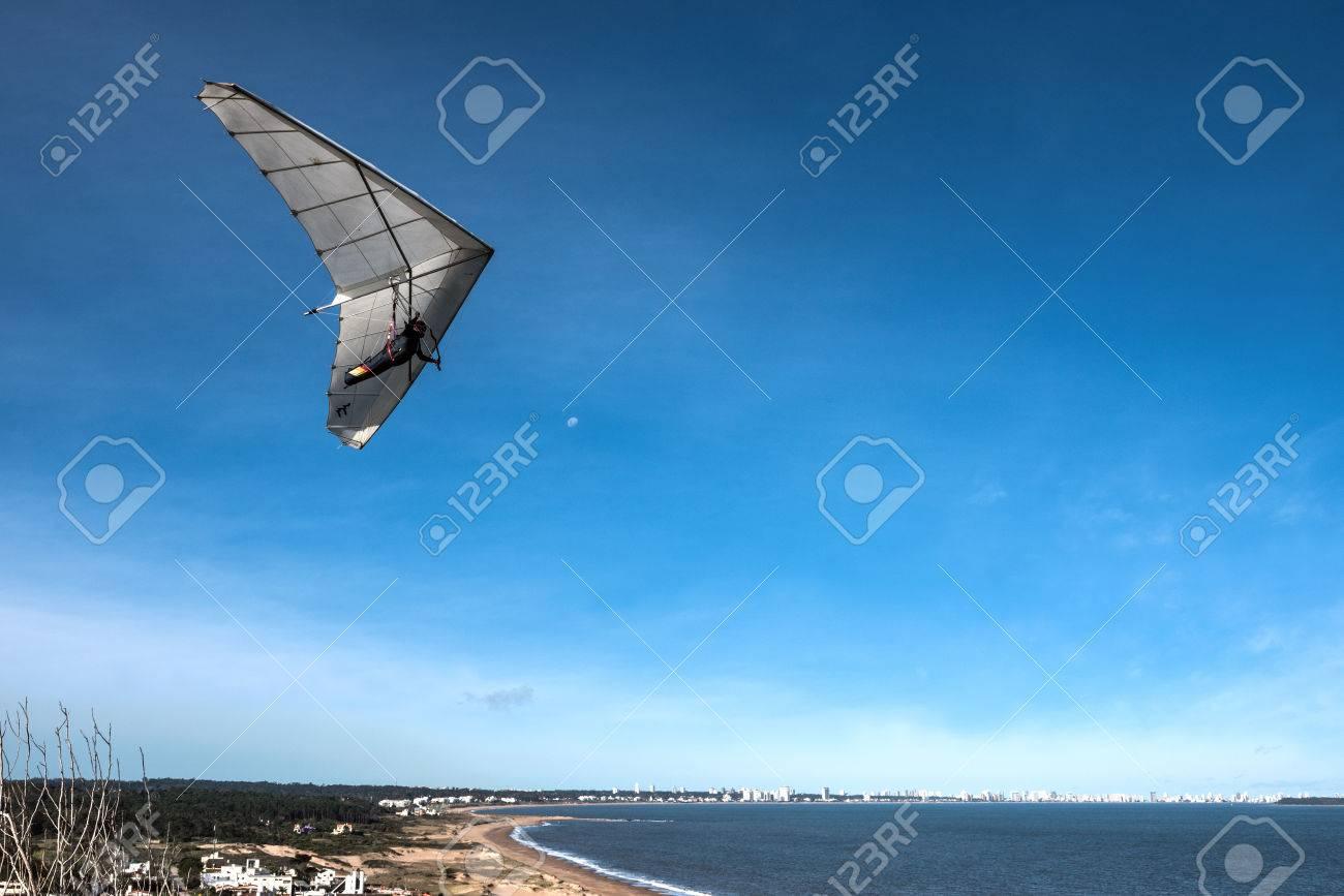 Punta del Este, the Atlantic Coast, Uruguay - August 2, 2017: Hang-glider flies over the Punta Ballena cape, against the background of the resort city of Punta del Este on the horizon - 83579771