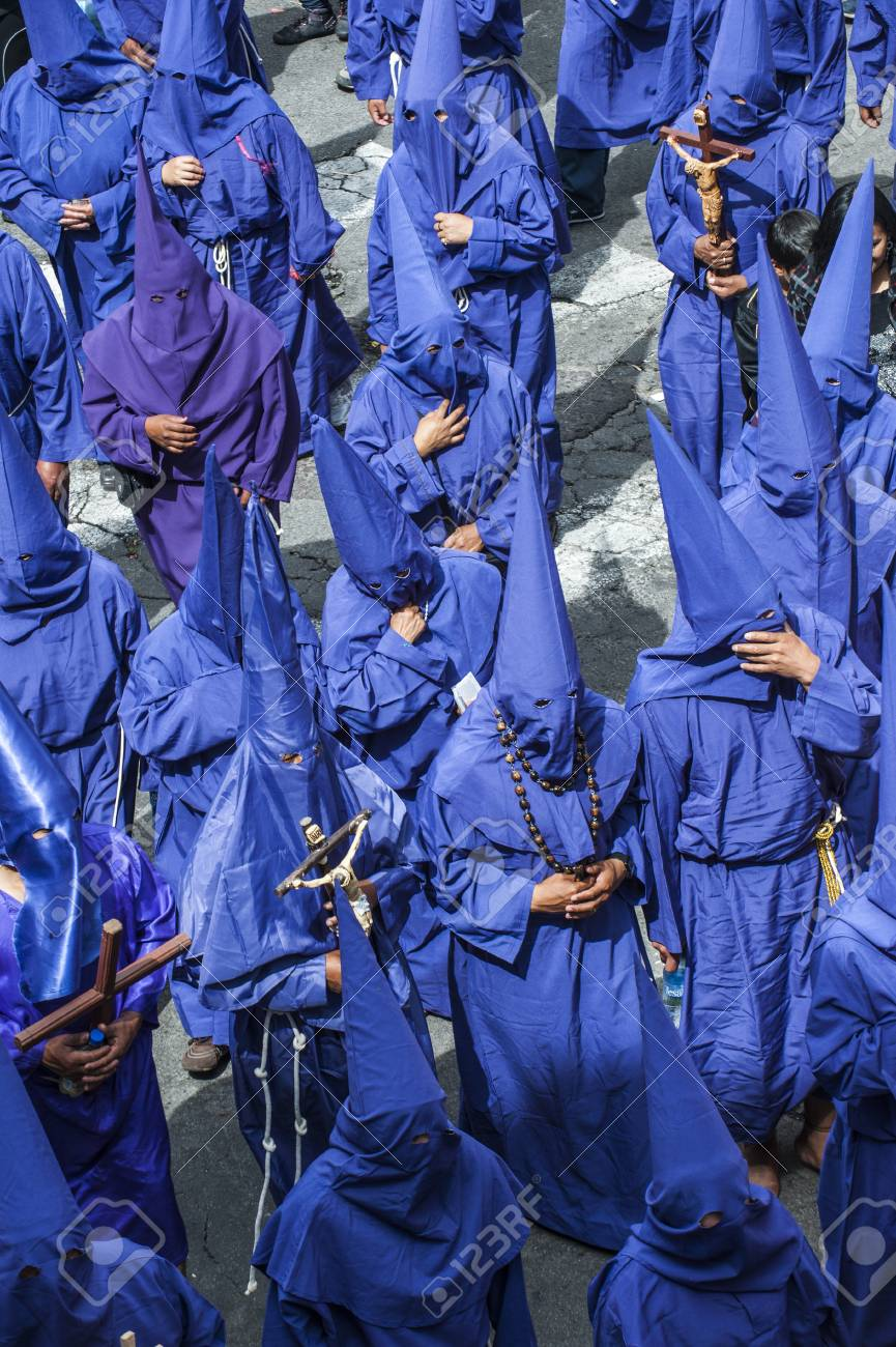 Quito, Ecuador - April 6, 2012: Catholic procession dressed in penitential robes with tall hoods to disguise their identity on Good Friday to remember the death of Jesus Christ, parading through the streets of the Old town. Holy Week (Semana Santa) is on - 90208138