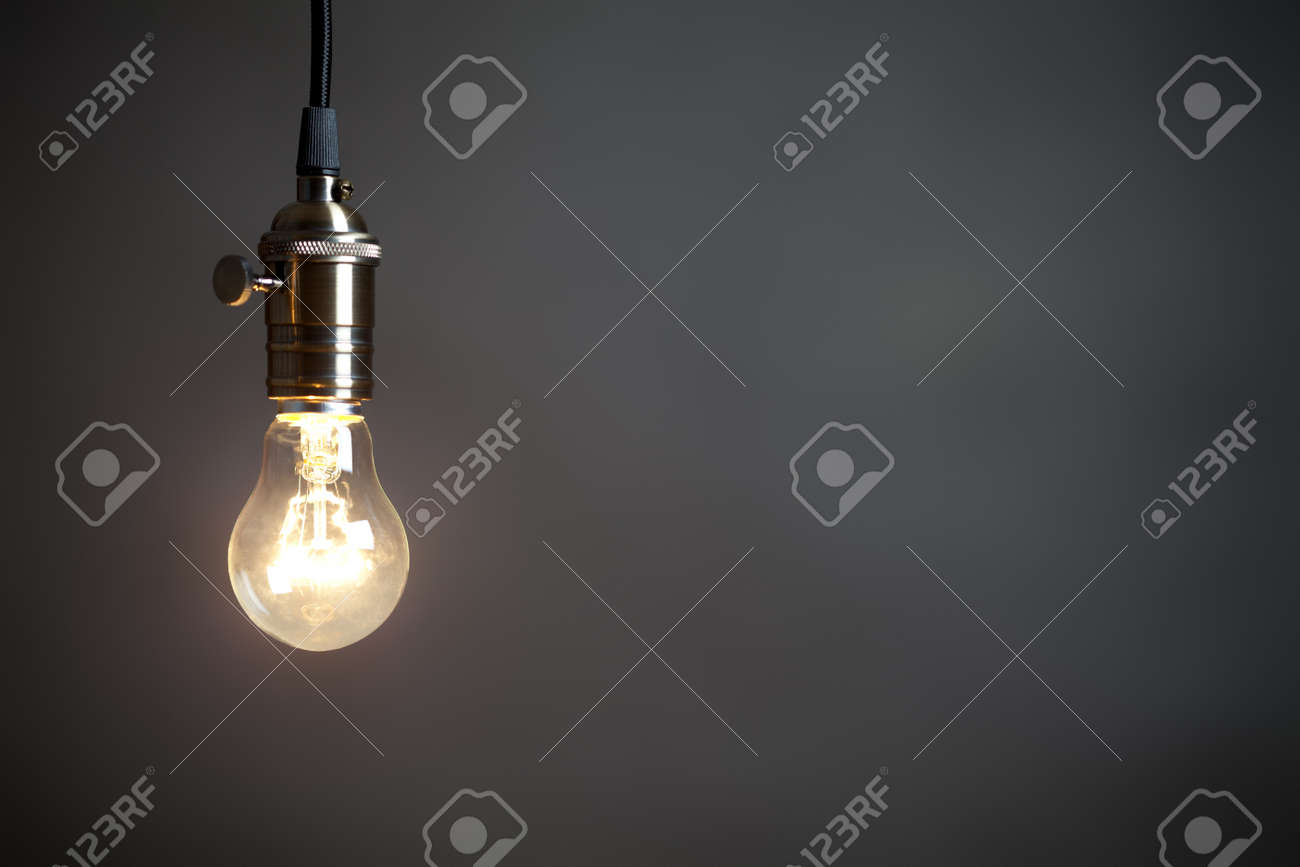 Vintage incandescent light bulb on gray background. On right is empty space to put text or something else. This file is cleaned and retouched. - 165287119