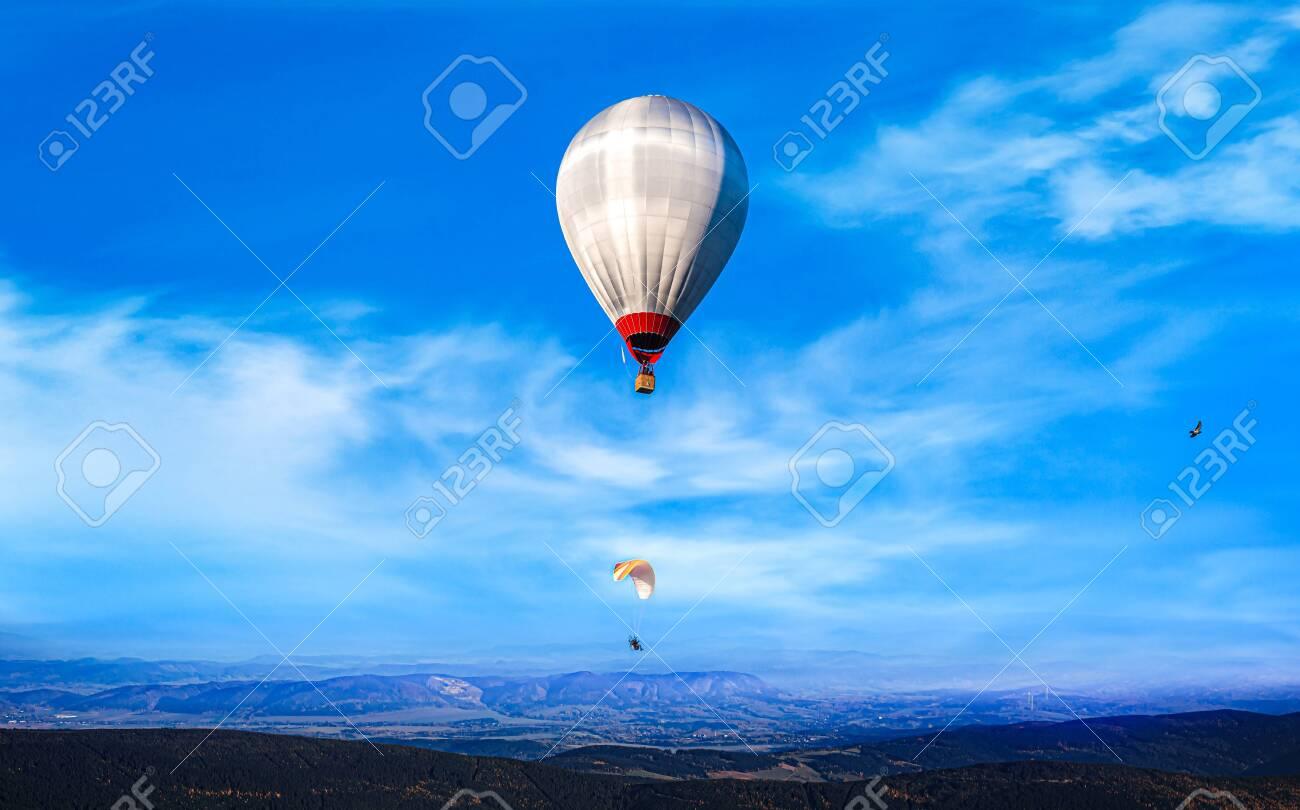 Balloon flies next to parachute. extreme sport. - 134643864