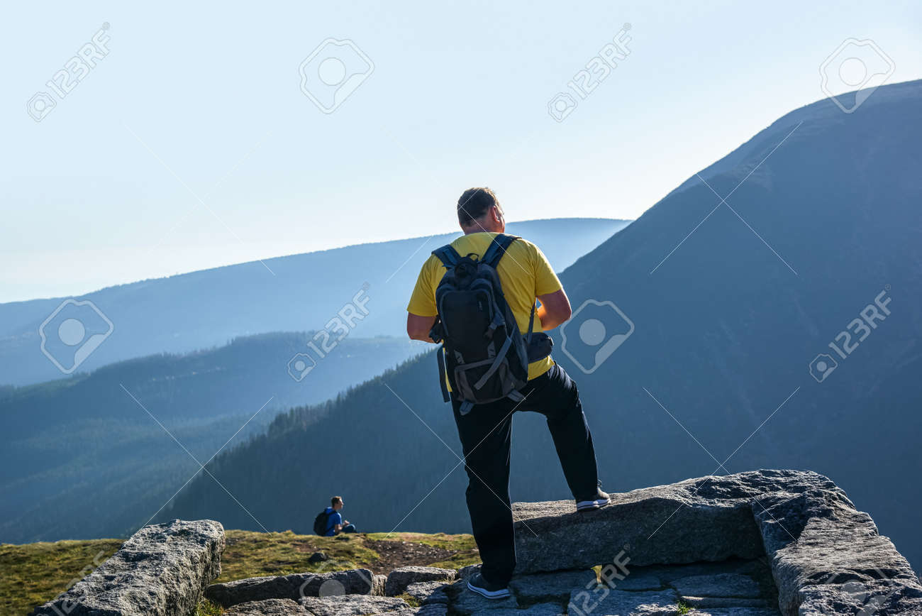 a man with a backpack on top of a mountain - 171845941