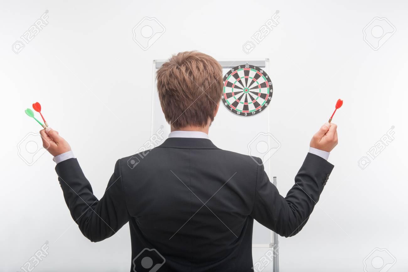 0de4dd39 Banque d'images - Demi-longueur portrait de l'homme aux cheveux noirs  portant la veste noire debout dos à nous et tenant fléchettes dans ses deux  mains