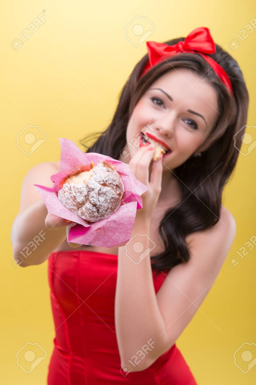 Half-length portrait of very sexy smiling dark-haired woman wearing great red headband biting the piece of appetizing short cake and showing it to us  Isolated on yellow background Stock Photo - 30716277