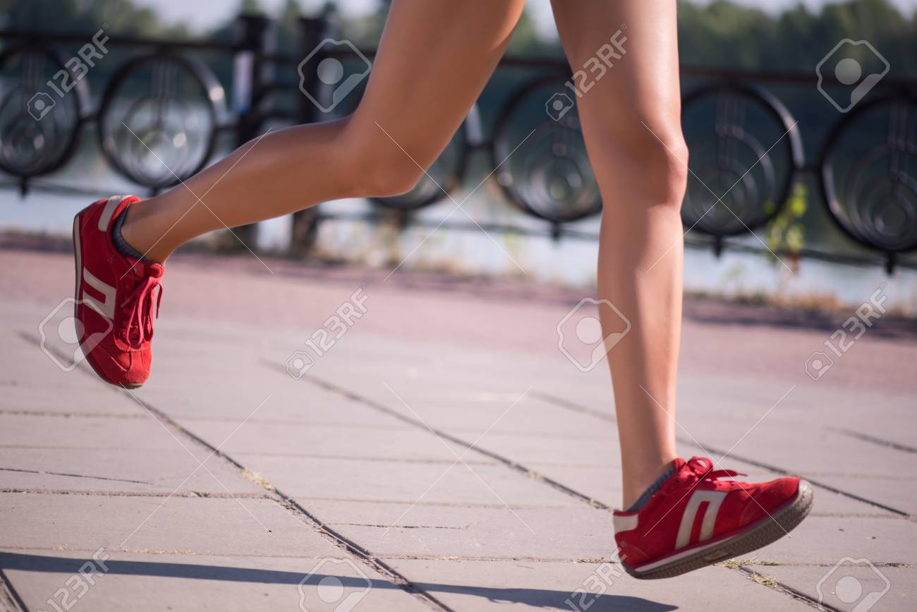 Selective focus on the perfect female legs wearing red jogging shoes running on the street - 32703758