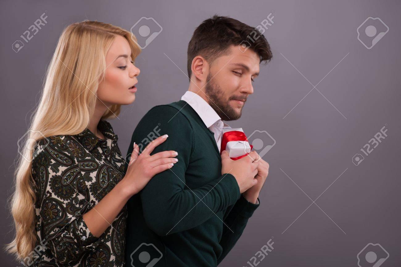 881d5e515a29 Brustbild von jungen Mann mit grünen Pullover und weißen Hemd beiseite  versteckt ein schönes Geschenk von
