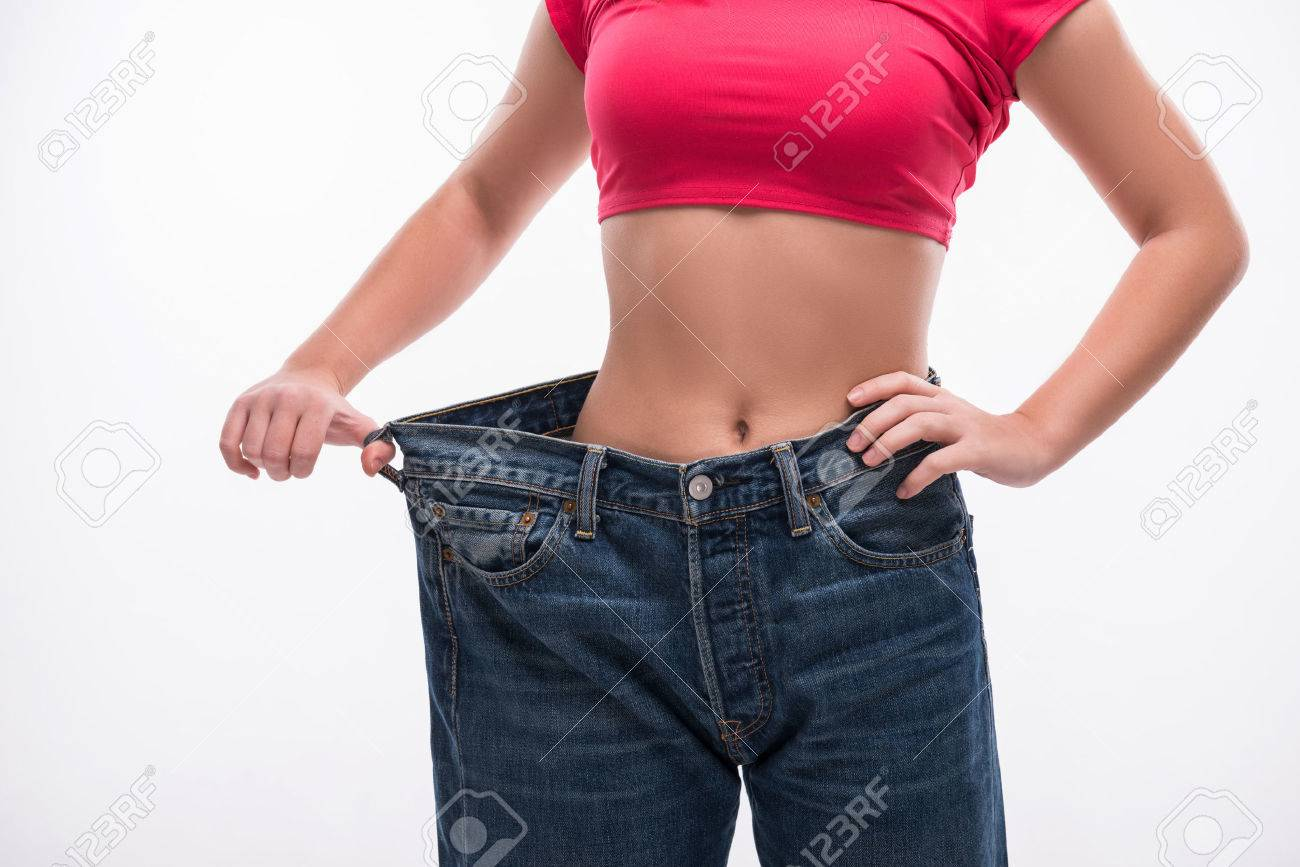 Close-up of slim waist of young woman in big jeans showing successful weight loss, isolated on white background, diet concept - 34868822